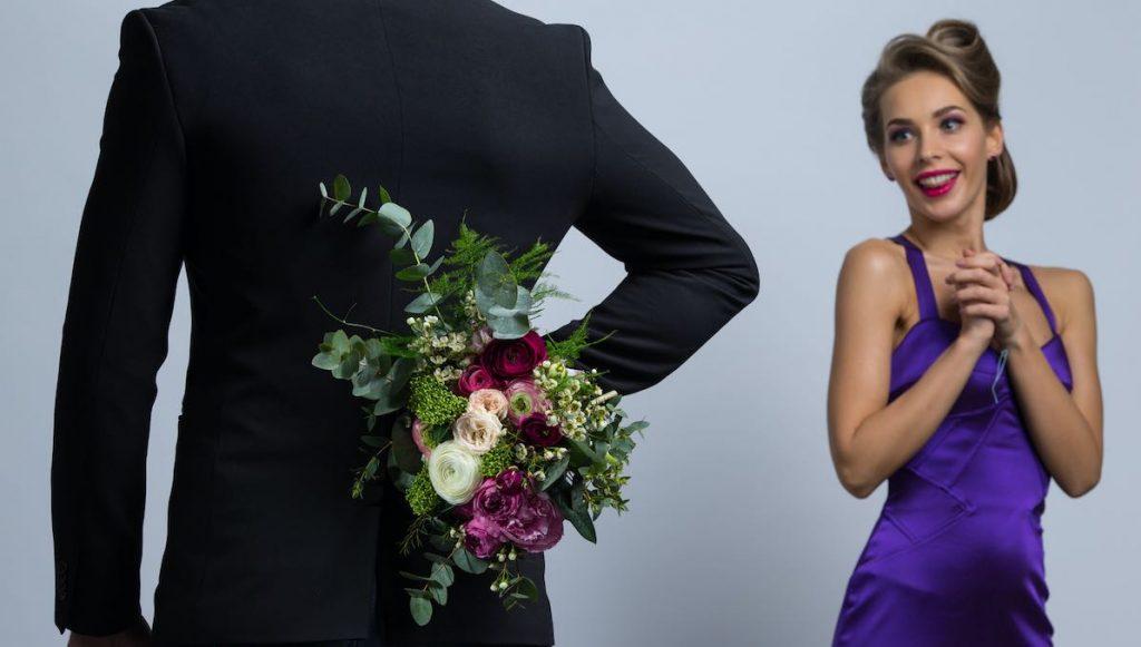 man brings flowers to woman