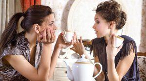 two pretty girl friends drink tea
